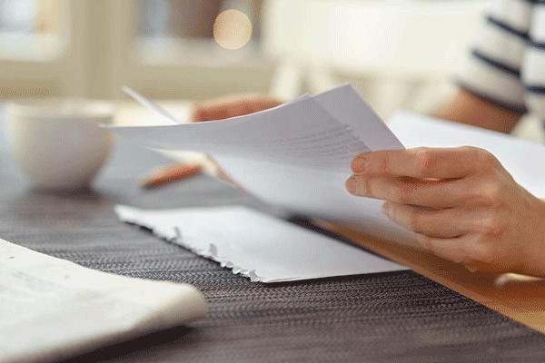 Auf diesem Bild ist eine Hand zu sehen, welche ein Blatt Papier hält. Es ist ein Symbolbild für Berwerbung schreiben.